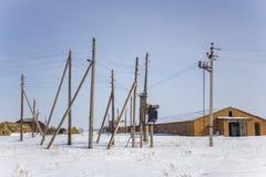 Utomhus- elektrisk transformator och en mängd av pelare med trådar mot ett lager i vinter arkivfoto