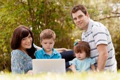 Utomhus- familj med datoren Fotografering för Bildbyråer