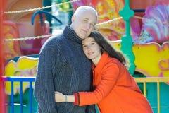 Utomhus- familjstående för nöjesfält av att krama den vuxna dottern och den höga fadern royaltyfri foto