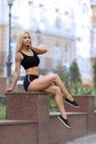 Utomhus- flickasammanträde och visning hennes buk- muskler Arkivfoton