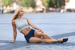 Utomhus- flickasammanträde och visning hennes buk- muskler Royaltyfri Fotografi