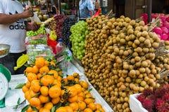 Utomhus- fruktmarknad med många olika asiatiska organiska nya frukter Arkivfoton