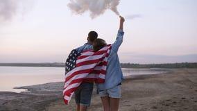 utomhus gå barn för folk Ung man och kvinna som täckas med amerikanska flaggan som passerar kusten Flicka i tillfälligt gå stock video
