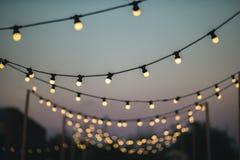 Utomhus gifta sig garnering med ljusa kulor på solnedgången Arkivbild