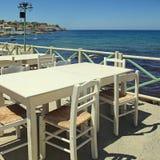 Utomhus- grekisk kaféterrass som förbiser havet, Kreta, Grekland Royaltyfri Fotografi