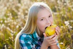 Utomhus- gullig flicka eller tonåring ätit sunt och saftigt päron fotografering för bildbyråer