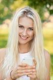 Utomhus- kvinna genom att använda en smartphone Royaltyfri Fotografi