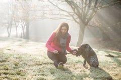 Utomhus- kvinna och hennes hundsträckning Konditionflicka och hennes husdjur som tillsammans utarbetar Royaltyfri Foto