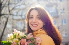 Utomhus kvinnlig st?ende av den attraktiva brunettflickan i det gula omslaget som rymmer en stor bukett av f?rgrika blommor som t royaltyfri fotografi
