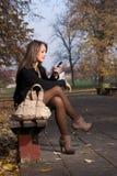 Utomhus- läsning för ung kvinna en SMS Royaltyfri Foto
