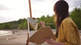 Utomhus- landskap för kvinnakonstnärmålning arkivfilmer