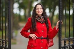 Utomhus livsstilstående av den eleganta och stilfulla seende unga förtjusande nya seende brunettkvinnan med röda kanter i rött la Royaltyfri Bild