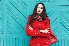 Utomhus livsstilstående av den eleganta och stilfulla seende unga förtjusande nya seende brunettkvinnan med röda kanter i rött la Royaltyfria Foton