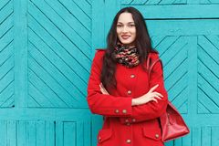 Utomhus livsstilstående av den eleganta och stilfulla seende unga förtjusande nya seende brunettkvinnan med röda kanter i rött la Royaltyfri Fotografi