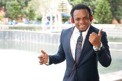 Utomhus- lyssna för affärsman till musik med hörlurar Royaltyfri Bild