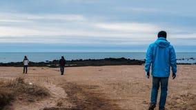 Utomhus- man som bär det blåa omslaget som går på den Island strandhorisonten Fotografering för Bildbyråer