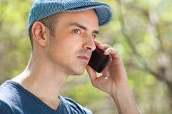 Utomhus- man som kallar genom att använda smartphonen Royaltyfria Bilder