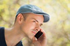 Utomhus- man som kallar genom att använda smartphonen Royaltyfri Foto