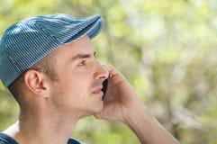 Utomhus- man som kallar genom att använda smartphonen Arkivbild