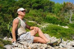 Utomhus- man som vilar på rock, når att ha fotvandrat Royaltyfri Foto