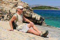 Utomhus- man som vilar på rock, når att ha fotvandrat Royaltyfria Foton