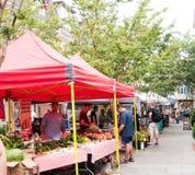 Utomhus- marknad för bonde` som s säljer frukt och grönsaker under tält arkivfoto
