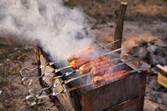 Utomhus- matlagning Smakliga korvar som grillas på en fyrpanna Royaltyfria Bilder