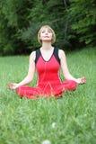 Utomhus- meditation för ung kvinna arkivbild
