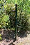 Utomhus- metall för utrustning för tappningallmänhetlekplatsen rostade delvist den gröna klättrapolen som omgavs med bevuxen skog royaltyfria bilder