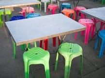 Utomhus- metalltabell och kulör plast- stol, gatamatplats i Thailand Royaltyfria Foton