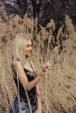 Utomhus- modefoto av den unga härliga damen i höstlandskap med torra blommor Royaltyfri Bild