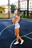 Utomhus- modestående av den nätta unga kvinnan med skateboarden arkivbilder
