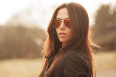 Utomhus- modestående av den unga brunettkvinnan i solglasögon arkivbild