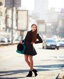 Utomhus- modestående av den sinnliga unga stilfulla damen för glamour som bär den moderiktiga nedgångdräkten, svart hatt Arkivfoto
