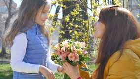Utomhus mottar videoen av den attraktiva unga modern en bukett av färgrika blommor från hennes lilla blonda dotter Lyckligt stock video