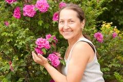 Utomhus- near blomstra buske för kvinna Arkivfoton