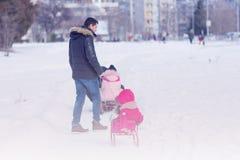 Utomhus- parkerar spela för fader och för dotter i vintersnö Fotografering för Bildbyråer