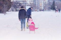 Utomhus- parkerar spela för fader och för dotter i vintersnö Arkivbilder