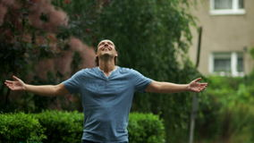 Utomhus parkerar ståenden av att le den unga mannen som tycker om varmt sommarregn i det offentligt, under en dag stock video