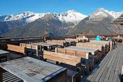 Utomhus- restaurang i mountainsnImagen med terrassen av a som omges av fjällängbergen, den lantliga wooden Fotografering för Bildbyråer