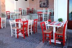 Utomhus- restaurang med den vita tabellen och röda stolar, Kreta, Greec Royaltyfri Foto