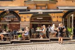 Utomhus- restaurang med många gäster som har matställen och en kvinnlig servitris Arkivbilder