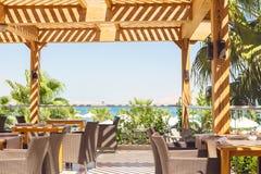 Utomhus- restaurang som förbiser havet och palmträden royaltyfri foto