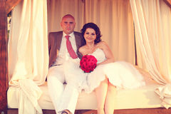 Utomhus- sammanträde för brud och för brudgum på en säng Royaltyfri Bild