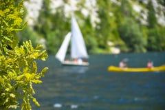 Utomhus- segling- och paddlaaktiviteter på en härlig bergsjö royaltyfri foto