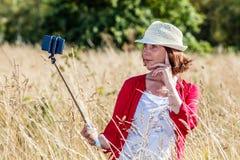 Utomhus selfie för härlig 50-talkvinna i högt torrt gräs Arkivbilder