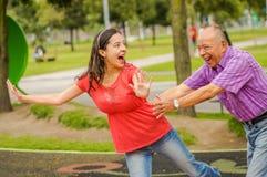 Utomhus- sikt av dottern och fadern som spelar på det fria i parkera som rymmer hennes midja arkivbild