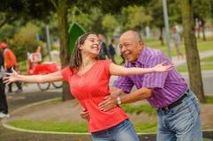 Utomhus- sikt av dottern och fadern som spelar på det fria i parkera som rymmer hennes midja fotografering för bildbyråer