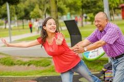 Utomhus- sikt av dottern och fadern som spelar på det fria i parkera som rymmer hennes midja royaltyfri fotografi
