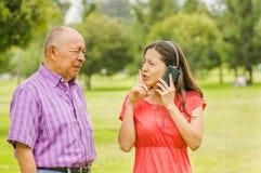 Utomhus- sikt av dottern som talar med hennes mobiltelefon, medan hans fader väntar på hennes daugher i parkera royaltyfri bild